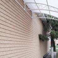 Обшитый дом сайдингом Стоун Хаус под кирпич от производителя Ю Пласт